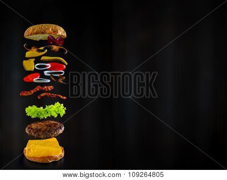 Hamburger stacked high with a juicy beef patty, cheese, fresh lettuce, onion and tomato with flying ingredients, space for text