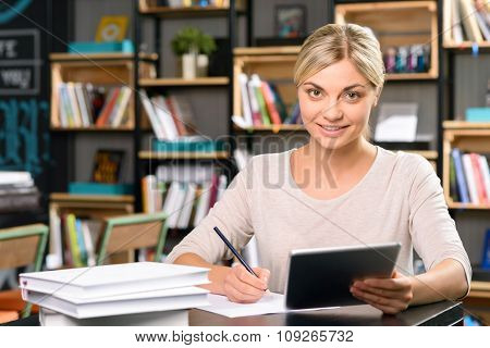 Young woman is working at the desk.