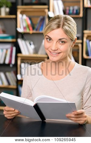 Young smiling woman is busy reading.