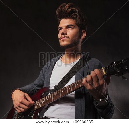 young artist playing guitar in black studio background while looking away