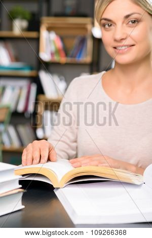 Young woman working with numerous books.