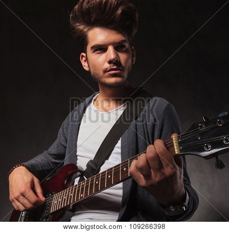 young cool indie artist playing guitar in studio background while looking away