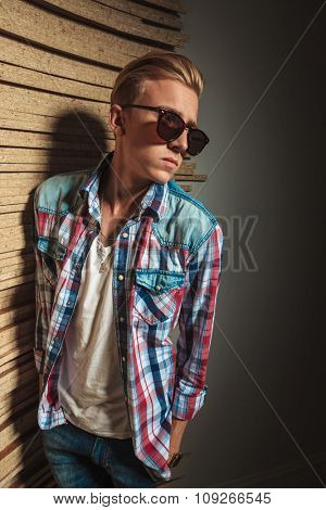 stylish blonde man posing in studio with hands in pockets while looking away