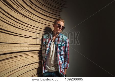 cool boy in studio background looking away while wearing sunglasses