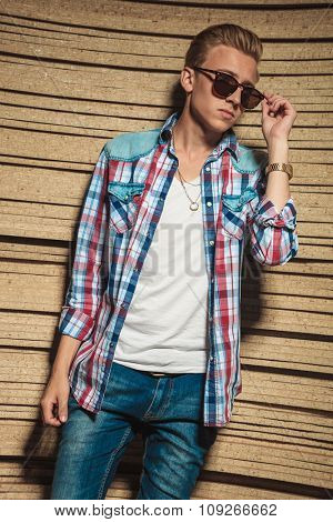 young man in studio background posing while fixing his sunglasses