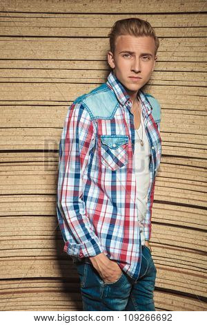 blonde guy leaning against studio background wall with hands in jeans pockets