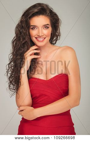 model with long curly hair posing while touching her chin
