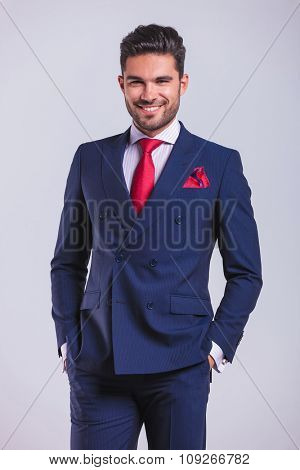 attractive business man smiling and posing with hands in pockets