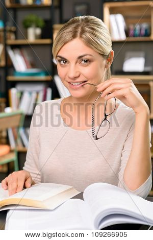 Smiling woman at the desk with lots of books.