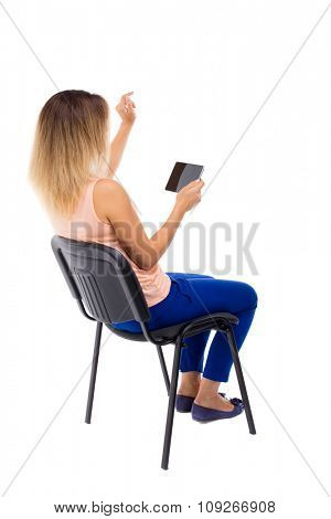 back view of pointing woman sitting on chair and looks at the screen of the tablet.  Rear view people collection.   girl is sitting on an office chair, working on a computer.