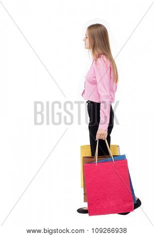 back view of going woman with shopping bags. beautiful girl in motion. backside view of person.  Isolated over white background. girl in the pink shirt is left bent under weight of bags.