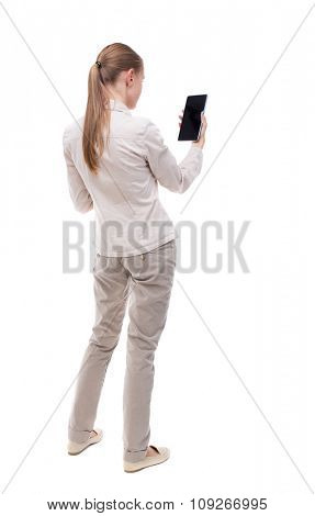 back view of standing young beautiful  girl with tablet computer in the hands of. girl  watching.   Isolated over white background. A girl in a white jacket vertically holding the Tablet PC.
