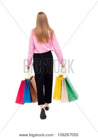 back view of going  woman  with shopping bags . beautiful girl in motion.  backside view of person.  Rear view people collection. Isolated over white background. A woman in a pink shirt goes distance
