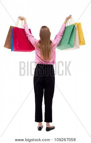 back view of woman with shopping bags . beautiful brunette girl in motion.  Rear view people collection. Isolated over white background. girl in pink shirt stands with arms raised to the top of bags