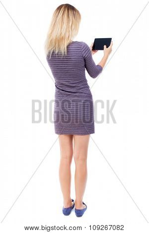 back view of standing young beautiful  girl with tablet computer in the hands of. girl  watching.   Isolated over white background. A girl in a short dress stands back and read e-books.