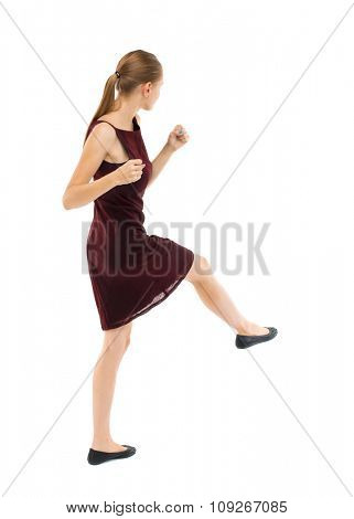 skinny woman funny fights waving his arms and legs. Isolated over white background. Blonde girl in a burgundy dress has foot.
