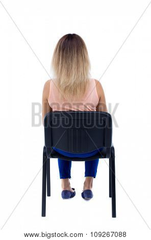 back view of young beautiful  woman sitting on chair.  girl  watching. Rear view people collection.  Isolated over white background. Blonde in blue pants sitting on an office chair and looking ahead.