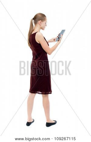 back view of standing young beautiful  girl with tablet computer in the hands of. girl  watching.  Isolated over white background. The blonde burgundy dress standing upright holding hands Tablet PC.