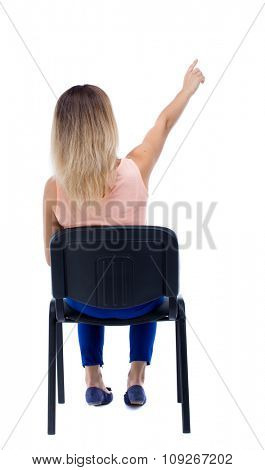 back view of young beautiful  woman sitting on chair and pointing.  girl  watching.   Isolated over white background. The girl is sitting on an office chair and shows up.-