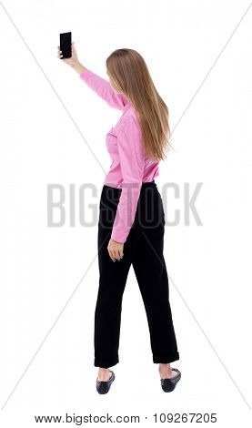 back view of standing young beautiful  woman  and using a mobile phone. girl  watching. backside view of person.  Isolated over white background. Turning left takes smartphone girl self.