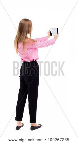 back view standing young beautiful  girl with tablet computer in the hands of.   backside view person. Isolated over white background. girl office worker in black trousers shoots video on your tablet.