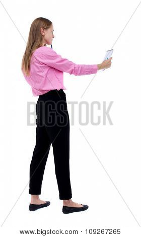 back view of  stands woman takes notes in a notebook. girl  watching. Rear view people collection.   Isolated over white background. Woman office worker in a pink shirt looks in a notebook.