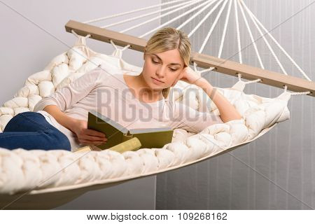 Young girl is reading while lying in the hammock.