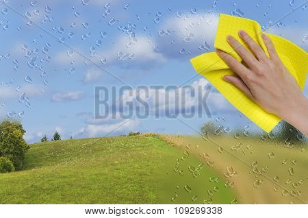 hand wiping off rainy window
