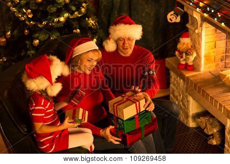 Christmas family in red hats with gift boxes