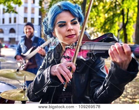 Music street performers girl violinist with blue hair playing  in city park  outdoor.