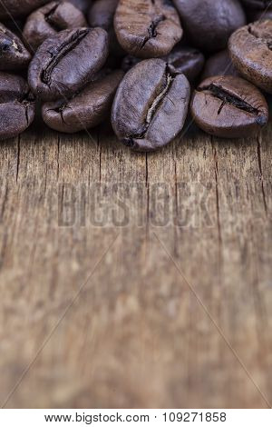 coffee grains on grunge wooden vertical background closeup