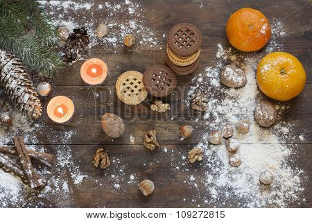 Tangerines and cookies in Christmas decor with Christmas tree, nuts and apples on dark wooden backgr