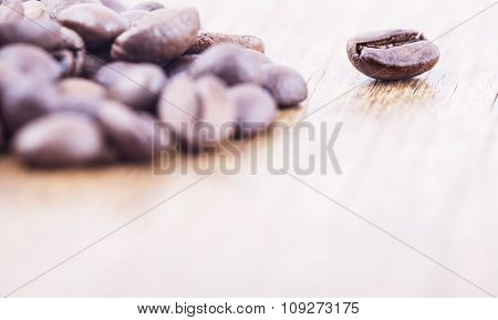 coffee grains on grunge wooden background. selective focus