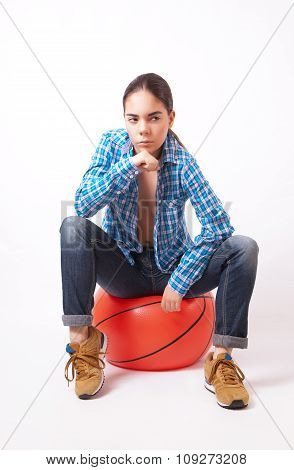 Woman In A Blue Shirt And Jeans Sitting On The Ball