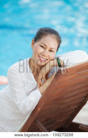 Woman relaxing in chaise-lounge