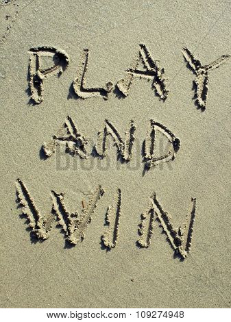 Play and win.Sport  message on  sand. Winning concept message