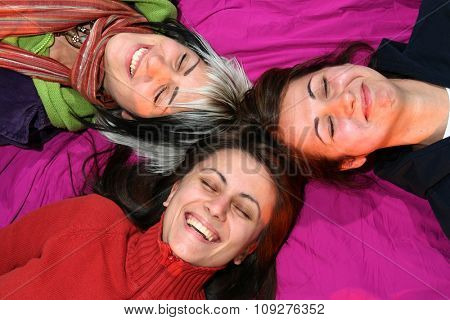 Women friends laying on ground smiling