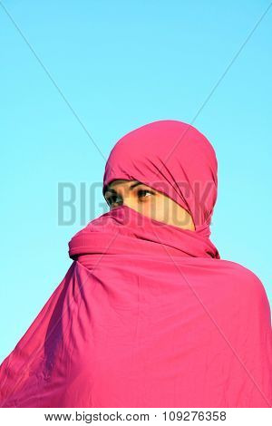 Mysterious muslim woman hiding her face behind white scarf and looking trought purple veil