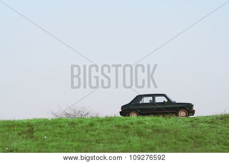Car going up the hill. Green slope