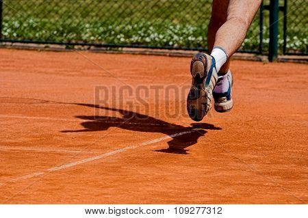 Tennis player and shadow on clay tennis court. Tennis concept