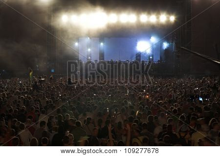 Crowd in blur at a rock concert. People in front of big concert stage