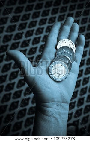 One euro coin money in hands on blue light. Business and economy concept