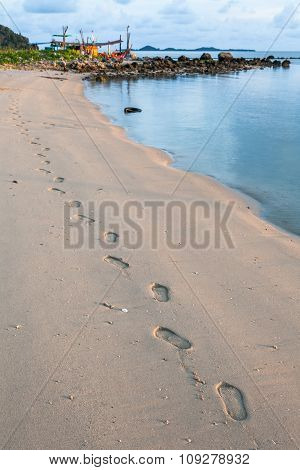 Human Footprints On The Sandy Beach At Sunset Time.