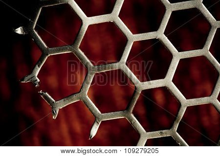 Metal hexagon grid pattern on red Background with missing part