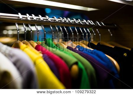 Clothes hangers with shirts in colors in store ready to buy. Fashion shopping concept
