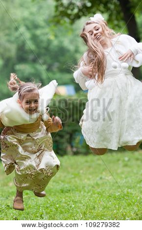 Two Little Beautiful Girls Jumping In A Park