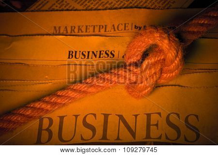 Business section in newspaper with big rope knot. World economic recession and depression concept