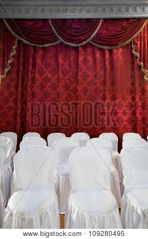 Red theater curtain and white chairs. Stage show presentation concept