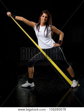 Young fitness  woman exercising in gym with rubber band  isolated on black
