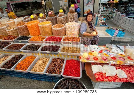Elderly Woman Sells Dried Fruit And Cottage Cheese On Rustic Street Market